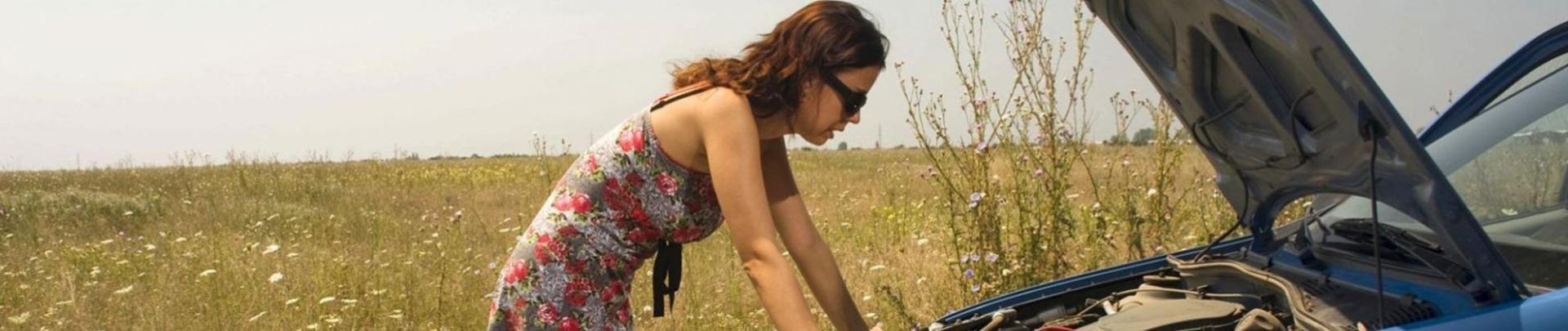 Vrouw staat met autopech langs de weg
